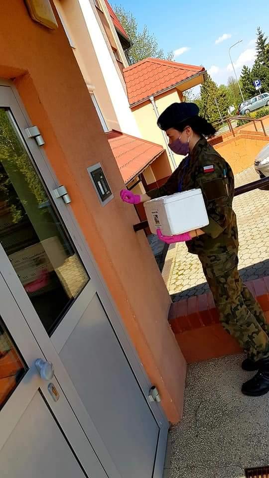 Przedstawiciel Korpusu Kadetó roznosi posiłki potrzebującym.